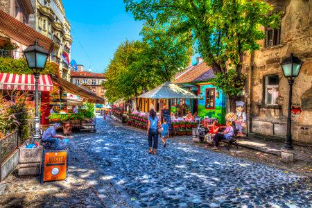 SERBIA, BELGRADE - SEPTEMBER 1: Restaurant Hat my in Skadarska street on September 1, 2017 in Belgrade. Old restaurants, cobblestones and lots of greenery. HDR Image. 新聞圖片