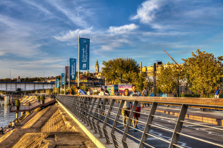 SERBIA, BELGRADE - SEPTEMBER 13: Promenade on Sava on September 13, 2017 in Belgrade. Bicycle and pedestrian trail on the promenade, bridge and church in the background.. HDR Image.