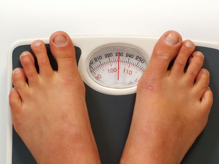 kilos: Ugly feet standing on measuring scales with a weight of 230 pounds104 kilos Stock Photo