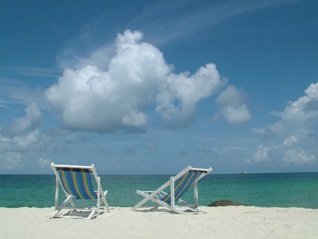 Two colourful deckchairs on a tropical island photo