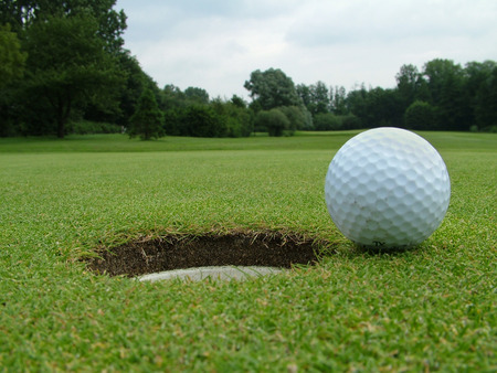 A Golf Ball on the edge of the hole photo