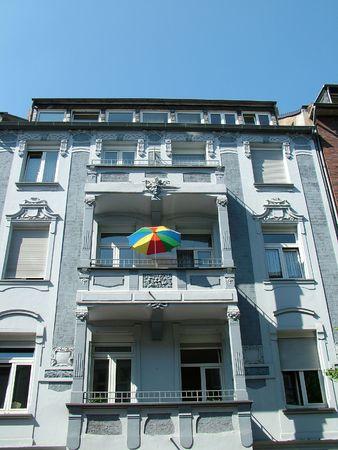 A brightly coloured umbrella on a city balcony photo