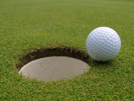 A golf ball just short of going into the hole photo