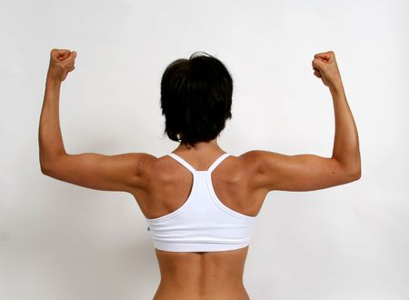 A tanned woman flexing her arm muscles photo