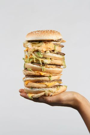 A massive burger held out on a hand photo