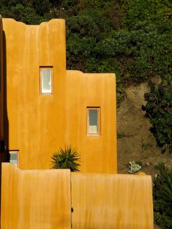 A terracotta colored house with a Mexican design photo