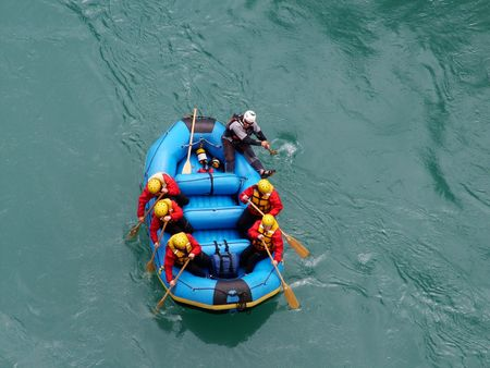 A group of people going white water rafting in Queenstown, New Zealand shot from above photo