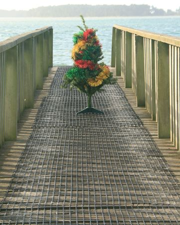 A decorated Christmas tree on a wooden pier photo
