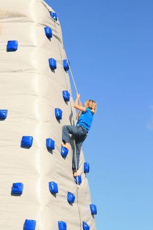 blowup: A young girl climbing up a blow-up climbing wall