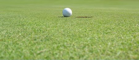 Panorama of a golf ball close to the hole photo