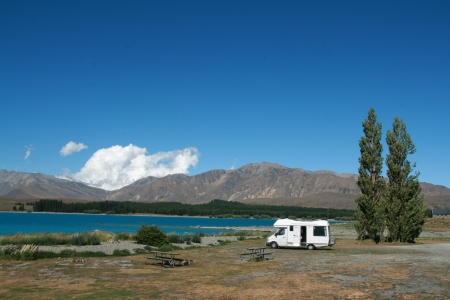 recreational vehicle: Pure white motorhome parked at the lake