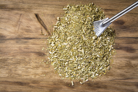 yerba mate: Dry yerba mate leaves on wooden table Foto de archivo