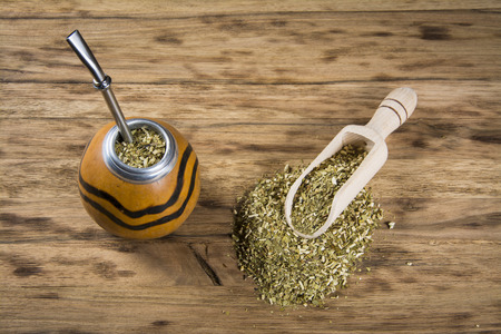 mate infusion: yerba mate cup on wooden table