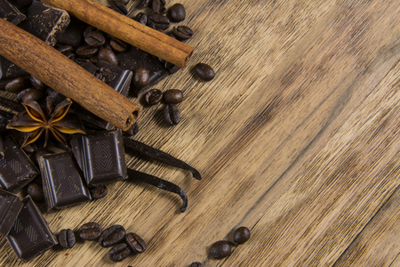 chocolate with cinnamon and caffe beans on wooden table