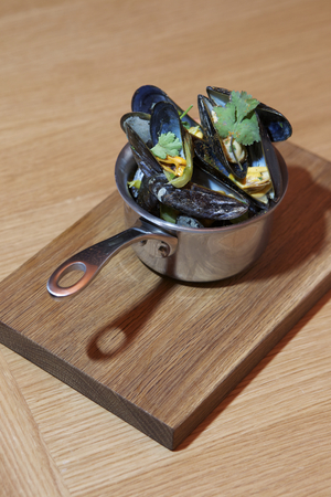 nether: fresh cooked moule with vegetables in the metal pot on the wooden tabl Stock Photo