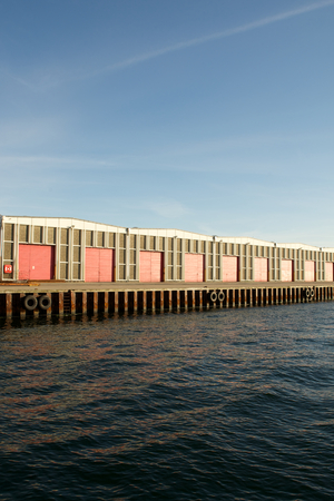 electricity export: industrial building with red gates on open sea or river Stock Photo