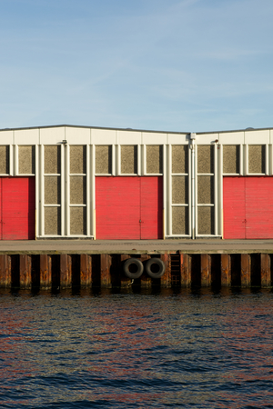 electricity export: front of industrial building with red gates on open sea space