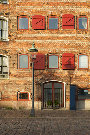 red shutters: brick wall with red framed windows with wooden shutters