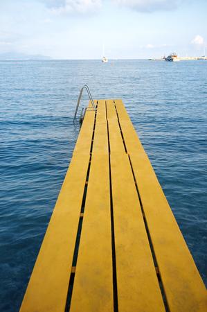 peer to peer: de largo por pares agua amarilla en la playa Foto de archivo