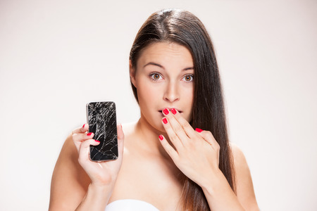 broken telephone: Young woman with broken smartphone. Stock Photo