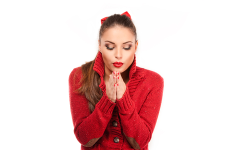 shiver: Portrait of a young attractive woman in red sweater trying to keep warm.
