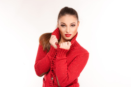 keep an eye on: Portrait of a young attractive woman in red sweater trying to keep warm.