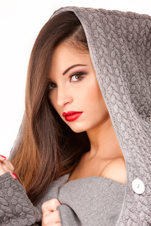shiver: Portrait of a young attractive woman in grey sweater with hood trying to keep warm.