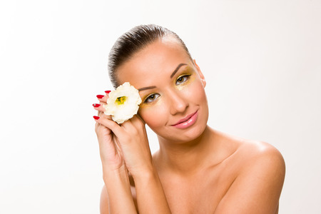 sleek: Gold make up. Brown sleek hair beautiful woman with white flower in hands close to face. Stock Photo