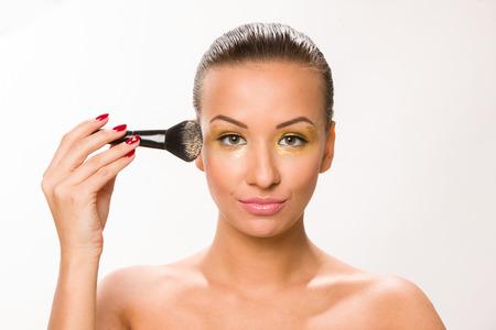 eyebrow raised: Make up. Brown sleek hair beautiful woman with fan brush close to face.