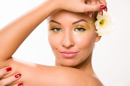 sleek: Gold make up. Brown sleek hair beautiful woman with white flower in behiond ear.