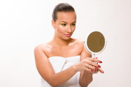 sleek: Gold make up. Brown sleek hair beautiful woman looking at mirror. Stock Photo