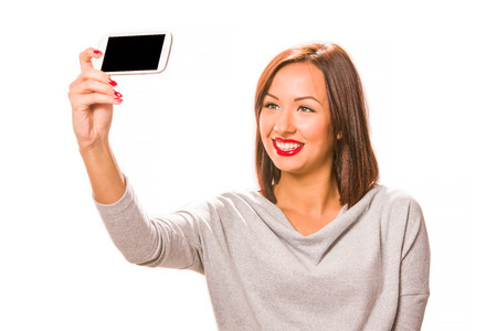 loose hair: Beautiful happy young woman taking selfie using smartphone.