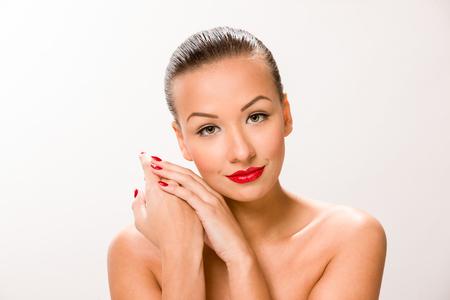 sleek: Brown sleek hair beautiful woman with hands close to face.
