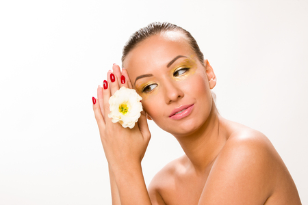 Gold make up. Brown sleek hair beautiful woman with white flower in hands close to face. Stock Photo