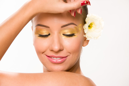 Gold make up. Brown sleek hair beautiful woman with white flower in behiond ear.