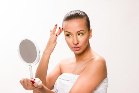 Gold make up. Brown sleek hair beautiful woman looking at mirror. Stock Photo