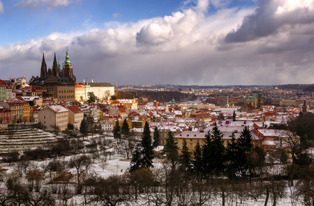 heavy snow: Amazing St. Vitus cathedral during winter day after heavy snow storm with snow cover at roofs. Sunny winter day in Hradcany district, Prague, Czech republic. Stock Photo
