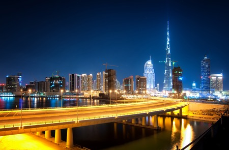 tallest bridge: Fascinating reflection of tallest skyscrapers in Business Bay district during calm night with amazing bridge. Downtown summer day. , Downtown, Dubai, United Arab Emirates.