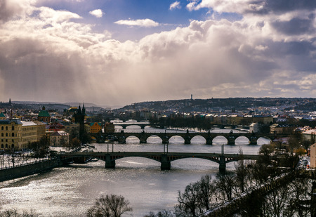 heavy snow: Amazing towers of Charles bridge and old town district with several bridges at Vltava river during winter day. Heavy snow storm and sunrays peeping through clouds, Prague, Czech republic