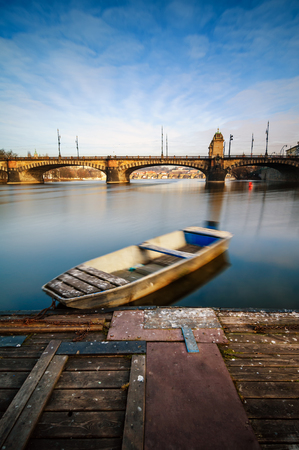 Amazing sunrise view at Vltava river bridge and boat with clear water reflection. Typical Prague sunny morning. Old town morning view. Prague Czech republic.