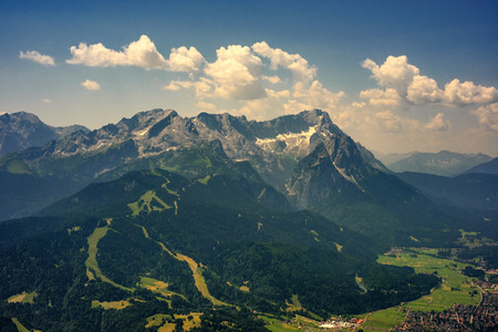 Beautiful view at highest mountain peak Zugspitze and Alpspix with Garmisch Partenkirchen from Wank mountain. Hot summer day and amazing cloudy sky. Bavaria, Germany.