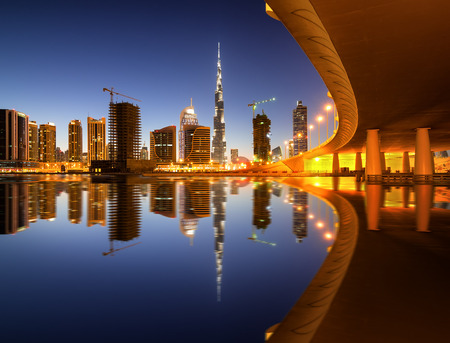 Fascinating reflection of tallest skyscrapers in Business Bay district during colorfull sunset near amazing bridge. Downtown summer day. Dubai, United Arab Emirates.