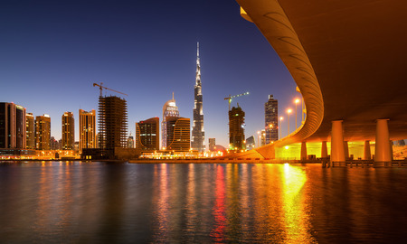 tallest bridge: Fascinating reflection of tallest skyscrapers in Business Bay district during colorfull sunset near amazing bridge. Downtown summer day. Dubai, United Arab Emirates.