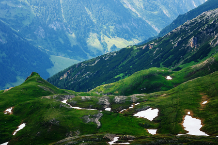 Detail of mountain landscape. Beautiful spring view at Grossglockner High Alpine Road Hochtor Pass. Green valley with snow. Highest mountain pass road in Austria.