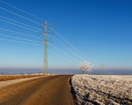 metal grid: Electric pylon in landscape. Sunny cold winter scene with tree and road on the outskirts of village. High voltage power lines in Czech republic. Stock Photo