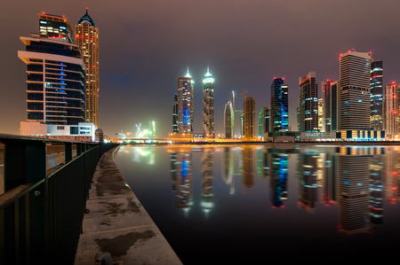 Fascinating reflection of tallest skyscrapers in Bussiness Bay district during cloudy night, Dubai, United Arab Emirates.