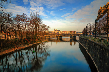Amazing sunrise view at St. Vitus cathedral and bridge with clear water reflection. Typical Prague sunny morning. Old town morning view. Prague Czech republic.