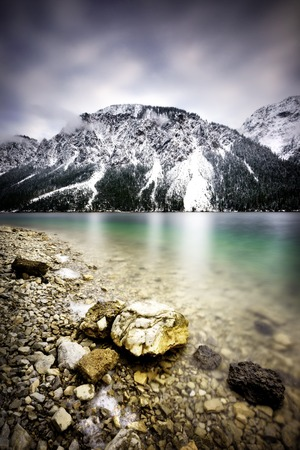 frozen lake: Landscape of Plansee lake and Alps mountains during winter, snowy view, Tyrol, Austria.