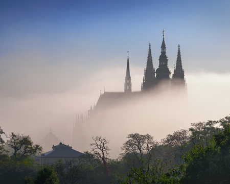 Fog waves over St. Vitus Cathedral during autumn, Czech republic. Imagens