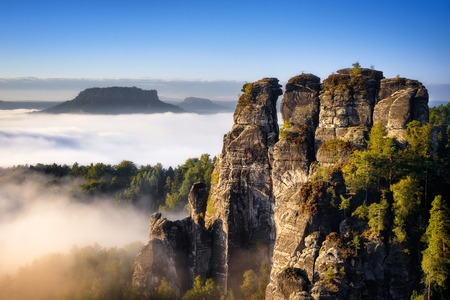 Rocky mountain view during autumn season. Foggy sunrise at Bastei, Saxon Switzerland, Germany